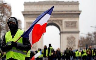 12月15日、パリの凱旋門前で黄色いベストを着てデモをする人の中にはフランス国旗を持っている人もいた=ロイター