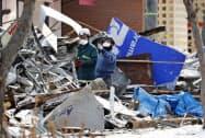 爆発のあった現場付近を調べる消防隊員ら(18日、札幌市豊平区)=共同