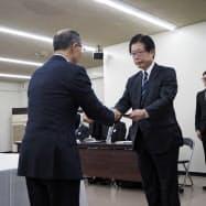JR北海道の島田社長(右)に沿線自治体側が廃線の同意書を手渡した(20日、月形町)