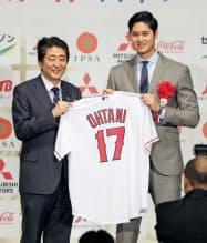 日本プロスポーツ大賞を受賞し、安倍首相(左)にユニホームを贈呈したエンゼルス・大谷(20日、東京都内のホテル)=共同