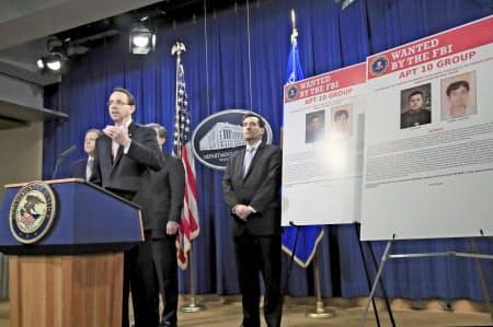 20日、訴追したハッカー2人の写真を横に会見するローゼンスタイン司法副長官(ワシントン)=AP