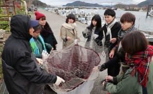 沖島の漁師(左)から漁に使う網の話を聞く学生たち(滋賀県近江八幡市)
