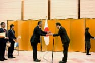 鈴木秀生外務省地球規模課題審議官(右)からトロフィーを受ける滋賀銀行の北川正義取締役(21日、東京・千代田の首相官邸)