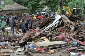 津波で破壊された家屋を調べる住民(23日、インドネシア・バンテン州)=AP