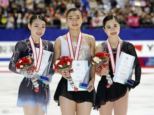 フィギュアスケートの全日本選手権女子で初優勝し写真に納まる坂本花織(中央)。左は2位の紀平梨花、右は3位の宮原知子(23日、大阪府門真市の東和薬品ラクタブドーム)=共同
