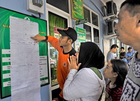 インドネシア・バンテン州で津波の犠牲者の名簿を見て泣く女性(23日)=ロイター・アンタラ通信