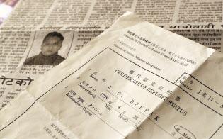 難民認定証明書(手前)と、来日前に拘束された時のことを報じるネパールの新聞=上間孝司撮影
