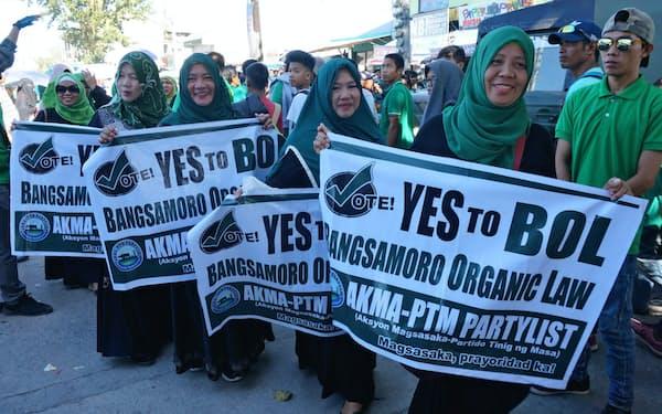 自治政府参加に「賛成」を呼びかける幕を手にしたイスラム教徒の女性(10日、フィリピン・コタバト市)