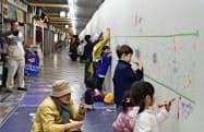 名古屋市の伏見地下街で開かれた「こども国際らくがきコンクール」で、工事用の仮設の壁に絵を描く子供たち(27日)=共同