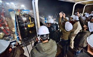建設中の八ツ場ダムを地元ガイドが夜に案内するツアーに参加した人たち(2018年12月、群馬県長野原町)
