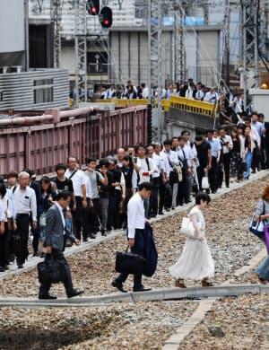 電車が止まり、線路を歩いてJR大阪駅に向かう人たち(6月、大阪市北区)