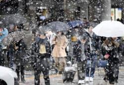 雪が降る中、名古屋駅前を歩く人たち(29日午前)=共同