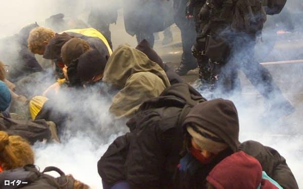 米シアトルのWTO閣僚会議場周辺でデモ隊を排除するための催涙ガスを放つ警察隊(1999年11月30日)=ロイター