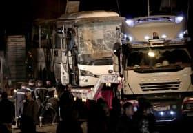 爆発の被害を受けたバスの近くを捜査する治安当局(28日、カイロ)=AP