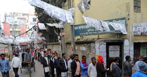 バングラデシュの首都ダッカの投票所前には30日、与党候補者のポスターの下、与党支持の有権者らが並んでいた