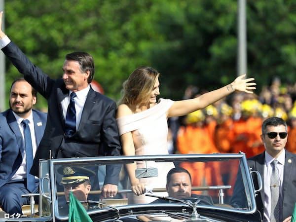 1日、就任式を終え国民に手を振るブラジルのボルソナロ大統領(左)(ブラジリア)=ロイター
