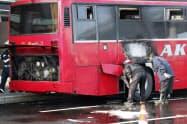 出火したバスの後部を確認する関係者(2日午前、釧路空港)=共同