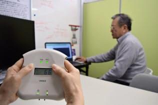 人さし指を機器に入れて疲労度を計測する(大阪市の疲労科学研究所)