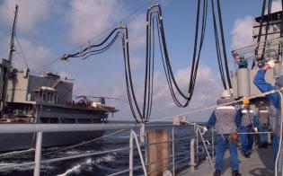 洋上給油のため補給艦「はまな」から米補給艦(左)に伸ばされる送油ホース(2002年2月20日、アラビア海)=共同