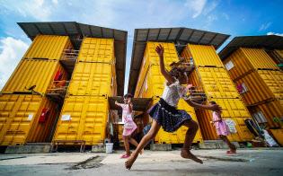 「コンテナ団地」の前で歓声を上げる子どもたち。120あまりのコンテナに約700人の移民労働者が暮らす(バンコク近郊)