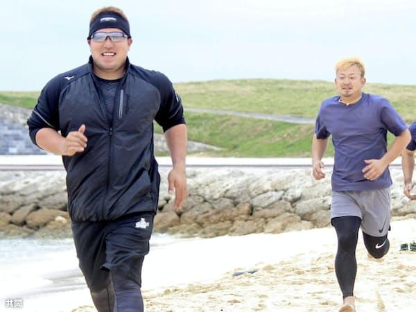 自主トレを公開し、砂浜を走る西武の山川(左)と森(8日、沖縄県宜野湾市)=共同