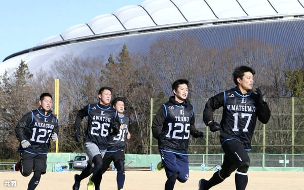 メットライフドームを背に走り込む松本(17)ら西武の新人選手たち(9日、西武第二球場)=共同