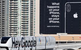 プライバシーに配慮していることを訴える米アップルの看板。下をグーグルの広告が入ったモノレールが走る(9日、米ラスベガス)=玉井良幸撮影