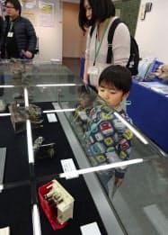 たんすの下敷きになって壊れた目覚まし時計(下)などが展示された企画展(8日、東京都新宿区の消防博物館)=共同