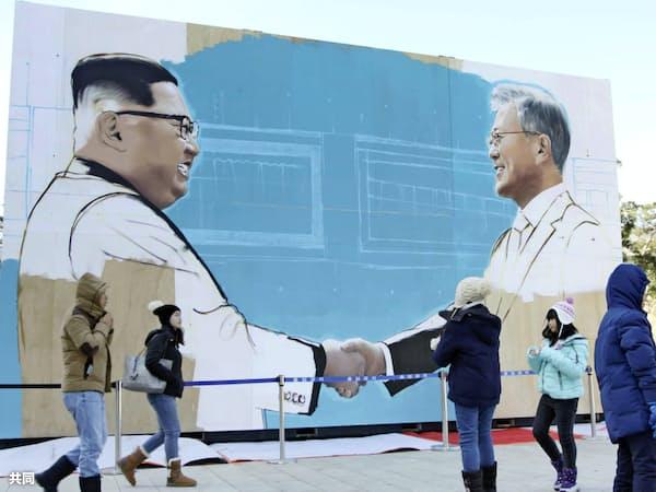 韓国大統領府前にある広場で作成中の文在寅大統領と北朝鮮の金正恩委員長が握手する絵(8日、ソウル)=共同