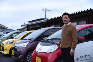 カーシェアリングに使う車の前に立つ吉沢さん(12月25日、宮城県石巻市)
