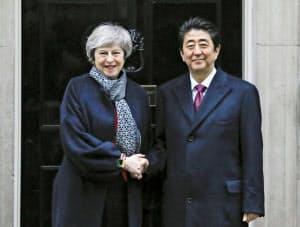 10日、会談前に握手する英国のメイ首相(左)と安倍首相(ロンドン)=共同