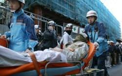 火災が発生したビル建設現場からけが人を搬送する消防隊員ら(11日午後、東京・新橋)