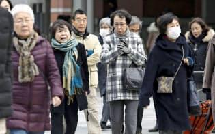 各地でこの冬一番の寒さとなり、防寒着に身を包んで歩く人たち=10日午前JR東京駅前、共同