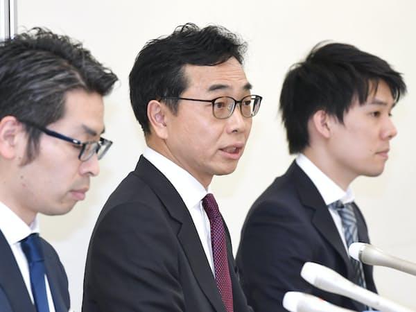 記者会見するコインチェックの勝屋敏彦社長(中)ら(11日午後、東証)