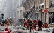 12日、パリ中心部のパン店で起きた爆発で、現場に駆け付けた消防隊員=ロイター