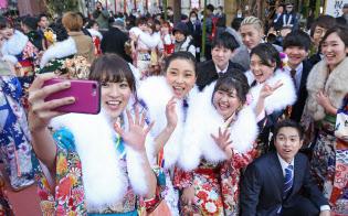 東京都台東区の成人式。会場前で振り袖やスーツ姿の新成人が記念撮影を楽しんだ(14日午前)=樋口慧撮影