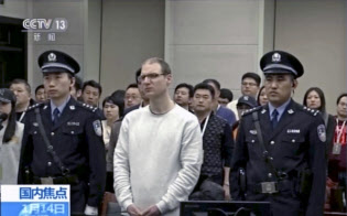 麻薬密輸罪に問われた大連地裁での差し戻し審で、死刑判決を言い渡されたカナダ人のロバート・ロイド・シェレンバーグ被告(中央。中国中央テレビから)=AP