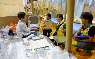 西日本豪雨の避難所となった小学校で活動する京都DWATのメンバーら(昨年7月、岡山県倉敷市)=京都府提供