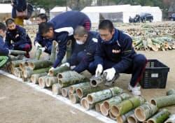 追悼行事の会場で竹灯籠を並べる高校生ら(15日午後、神戸市)=共同