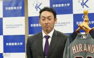 母校の京産大を表敬訪問し、自身のユニホームの前で写真撮影に応じるダイヤモンドバックスの平野佳寿投手(16日、京都市)=共同