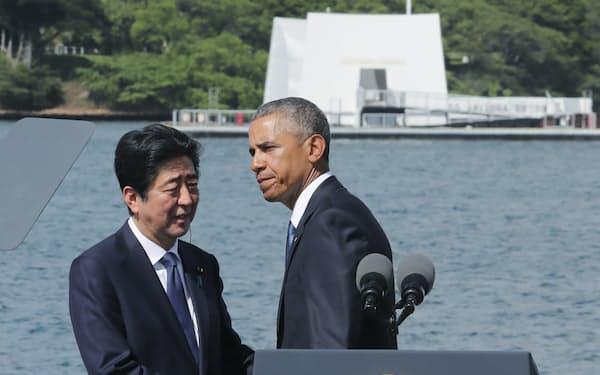真珠湾のアリゾナ記念館(奥)を訪れ、演説後に握手する安倍首相とオバマ米大統領(2016年12月、米ハワイ州オアフ島)