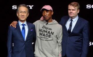 人気プロデューサーのファレル・ウィリアムス氏(中)らと撮影に応じるソニーの吉田憲一郎社長=左(7日、米ラスベガス)