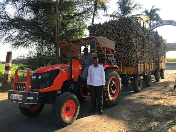 収穫したサトウキビを荷台に載せ、クボタのトラクターで製糖工場に運ぶ農家(18年12月、インド西部マハラシュトラ州)