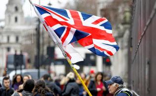16日、ロンドンの英議会前で英国旗を持つ男性=ロイター