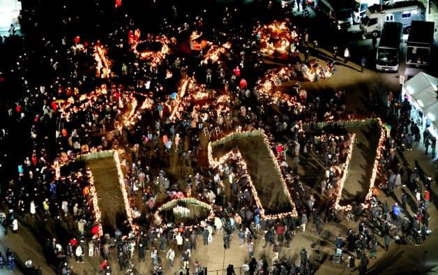 竹灯籠にろうそくの灯がともされ、浮かび上がった「1.17」の文字(17日午前、神戸市中央区の東遊園地)