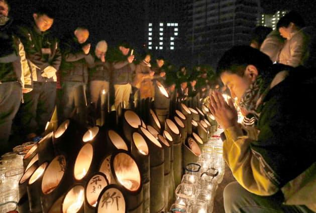 犠牲者の冥福を祈る人たち(17日午前5時46分、神戸市中央区)