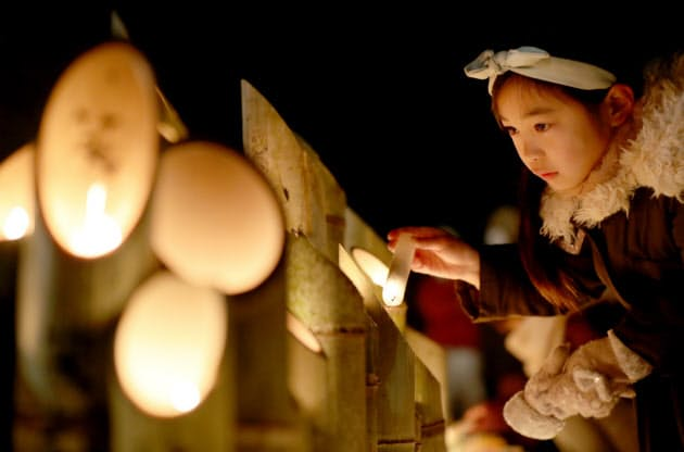 竹灯籠に灯をともす森川卯希ちゃん(7)。小学校で震災のことを学び、初めて参加した(17日午前、神戸市中央区)