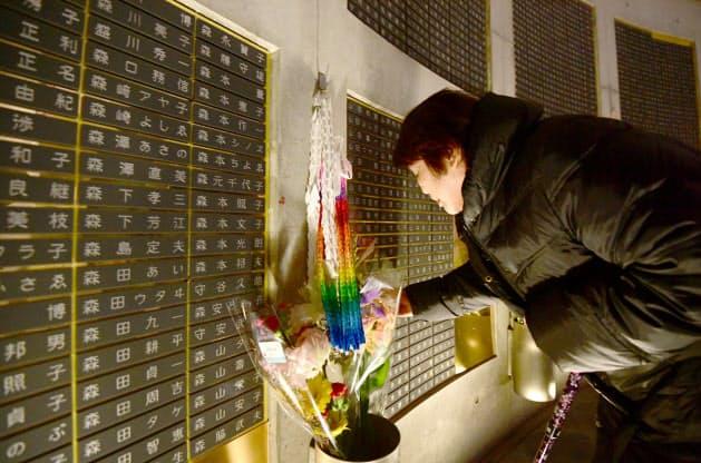 「慰霊と復興のモニュメント」にある娘の名前が刻まれた銘板を手でなでる山谷つや子さん(79)。「ずっと見守ってくれていてありがとう」と声をかけた(17日午前、神戸市中央区)