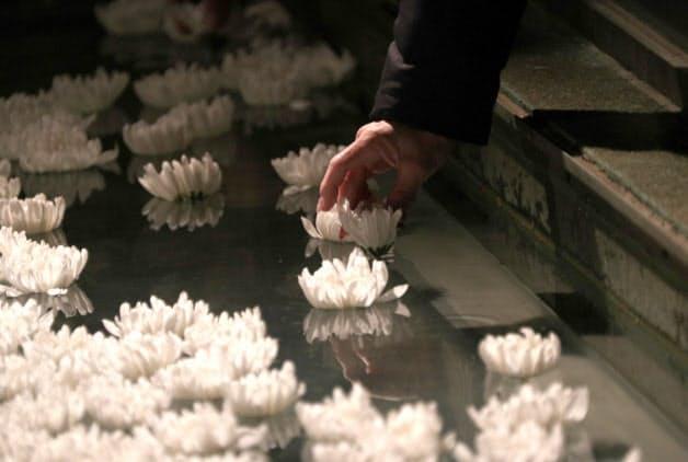 「慰霊と復興のモニュメント」の水盤に手向けられた花(17日午前、神戸市中央区)