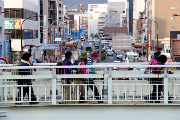 幹線道路の国道2号を渡る「1.17ひょうごメモリアルウォーク」の参加者(17日午前、兵庫県西宮市)